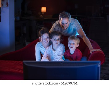At home by night, Cheerful family sitting in a red couch and watching a funny movie on tv. They are laughing togetherness