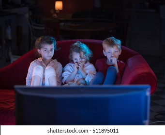 At home by night, three scared kids watching tv