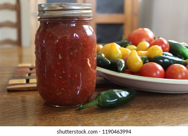 home canned salsa in glass jar with tomatoes and peppers