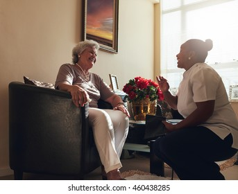 Home caregiver talking with a senior woman sitting on chair at home. Female nurse visiting senior female patient home for routine checkup.