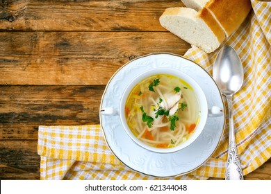 Home chicken soup with noodles, vintage spoon, tablecloth, bread on a wooden table, rustic style, top view.