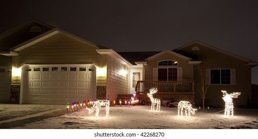 Home with Christmas Lights on a snowy night.