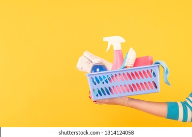 Home cleaning products. Housekeeping concept. Hand holding a basket with supplies. Copy space on yellow background.