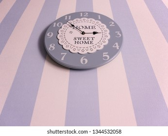 Home clock on the wall with striped wallpaper