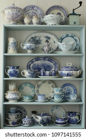 Home collection of old antique, vintage tableware, dishes, old pottery, transfer ware, china pottery, kitchen utensils  with craquelure and patina from faience, porcelain, ceramic on wooden shelf
