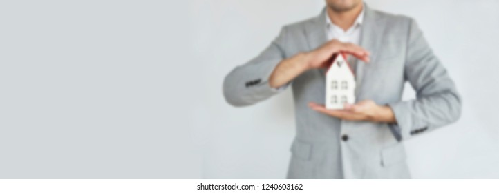 Home Concept : Blur A man holding white mock up home on his hand for sale with  Copy space. Real estate agent with house model at Metal. New house. Renovate. Construction Building. Housing loan.