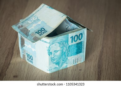 Home concept made from hundred Brazilian reais banknotes