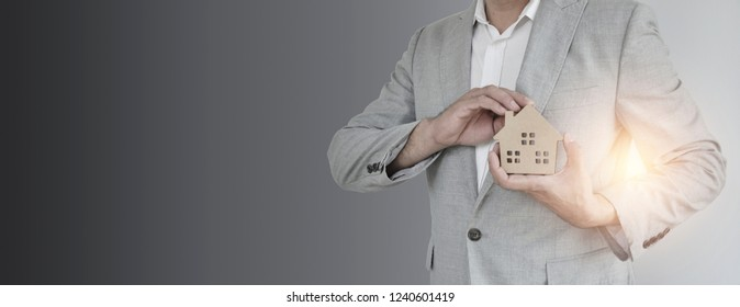 Home Concept : A man holding white mock up home on his hand for sale with  Copy space. Real estate agent with house model at Metal.  New house. Renovate. Construction Building. Housing loan. Mortgage.