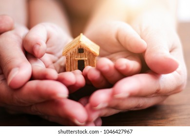 Home concept,people, family and home concept - close up of woman and boy holding model house