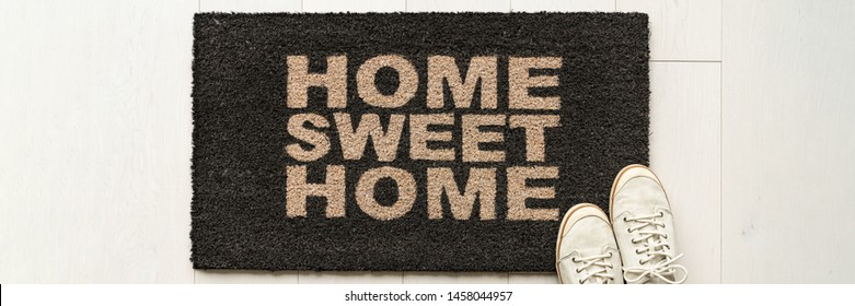 Home condo door mat sweet home doormat text at condo entrance with casual shoes panoramic banner. House move in concept.