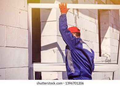 home construction loader worker carries a platic window for installation repairs
