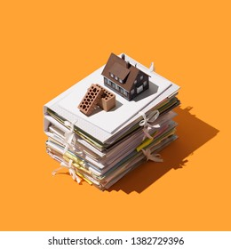 Home construction and real estate: pile of paperwork, bricks and model house