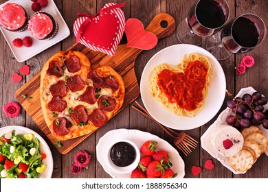 Home cooked Valentines Day dinner. Top view table setting on a dark wood background. Heart shaped pizza, pasta, wine, cheese plate and desserts.