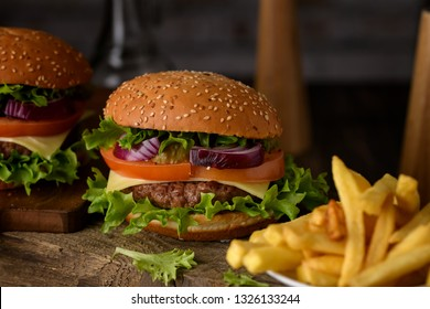 Home cooking burgers and french fries with your hands on a dark wooden background.