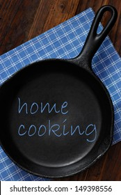 Home cooking concept with text added to still life of vintage cast iron skillet on rustic background.  Ideal for use as menu design or cookbook cover.