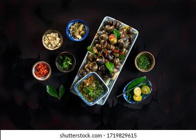 Cuisine maison Oc Luoc Mam Gung. Escargot bouilli avec feuilles de citron vert, piment et sauce au gingembre, dans une cuisine vietnamienne sombre. Cuisine asiatique.