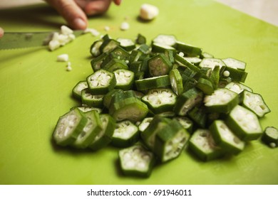 Home cooking, okra fruits cut onto small pieces; chopping garlic cloves;