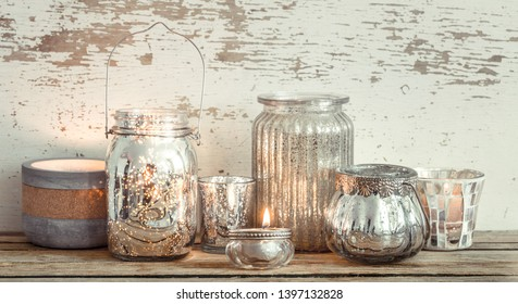 Home cozy beautiful decor, different vases and candles on a wooden background , the concept of interior details