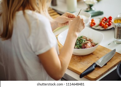 Home cozy kitchen chef pours salt on pork or beef meat with salt shaker Barbecue concept or healthy meat lifestyle shot