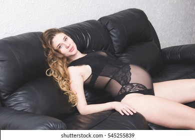 Home cozy portrait of pregnant woman with sexy body resting at home on sofa
