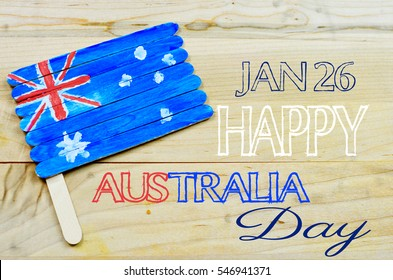 A home crafted red, white and blue Australian flag painted on popsicle sticks on a wooden background. Text added for Australia Day celebration in January.
