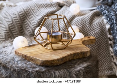 Home deco indoor with candle holder and light bulbs, cozy blanket and faux fur,cozy winter interior details