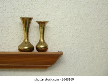 Home decor - brass vases on oak shelf in front of knock-down textured wall
