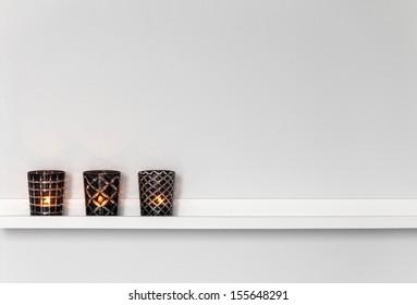 Home decor, candle lights on a white shelf.