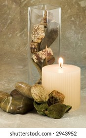 Home decor collection of candle, vase and stones and potpourri on brown print