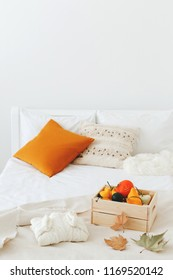 Home decor. Cozy fall bedroom interior: white wall, bed with white linen, light beige plaid, orange pillows,  wooden box with pumpkins, dry autumn leaves, sweater. Autumn decoration.