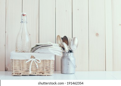 Home decor: glass bottle and wicker basket and vintage cutlery on a wooden board background, cozy kitchen arrangement in retro style, soft pastel colors.