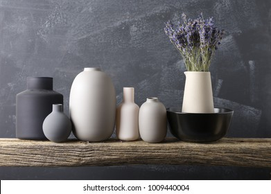 Home decor - neutral colored vases with lavender bouquet on rough distressed wooden shelf against grey wall.