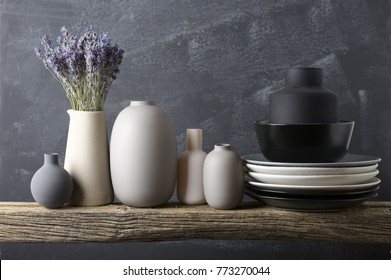 Home decor - neutral colored vases with lavender bouquet and dishware on rough distressed wooden shelf against grey wall.