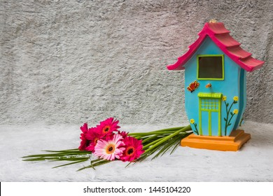 Home decor with pink flowers and a bird house