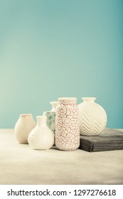 Home decor - various light colored vases on gray concrete background against blue wall. Copy space, retro style toned.