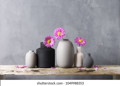 Home decor - various neutral colored vases with pink flowers on rough distressed wooden shelf against grey wall.