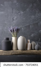 Home decor - various neutral colored vases with lavender bouquet on rough distressed wooden shelf against grey wall.
