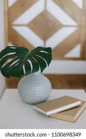 Home decoration. A book and a palm leaf in vase on the table. flat lay