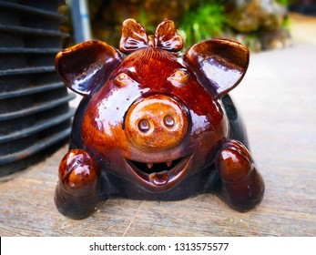 Home decoration concept. Large brown ceramic smiling pig, it was placed on the cement floor to welcome guests at the entrance. Selective focus and copy space.