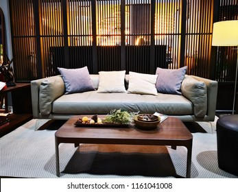 Home decoration concept. The living room is separated by slats. there is a wooden table, a lamp and a gray sofa with cushions. the floor is covered with gray carpet.