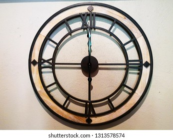 Home decoration concept. Wall clock that is made of black steel Which has 4 Roman numbers. It is hung on a light brown wall. Selective focus and copy space.