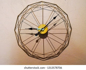 Home decoration concept.The wall clock has no numbers that are made of wood, iron and copper wire being hung on a light brown wall. Selective focus and copy space.