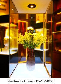 Home decoration concept. The yellow flower bouquet is in a brown vase. Which wasplaced in the showcase. Selective focus and copy space.