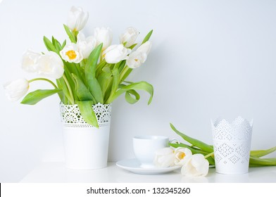 Home decoration, fresh white tulips in a vase and a cup on a white table, close-up