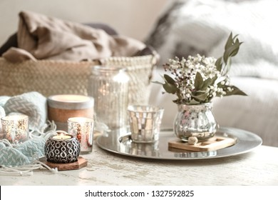 Home decorations in the interior. On the wooden background lies a turquoise blanket and wicker basket with a vase of flowers and candles. Concept of comfort