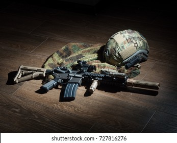 Home Defense. The Black Rifle.  SBR with sound suppressor and tactical bulletproof helmet on the floor.