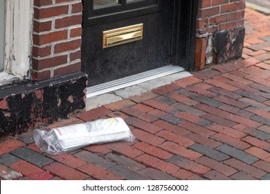 Home delivered newspaper on a brick sidewalk, with a front door in the background and space for text on the right