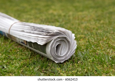 A home delivered newspaper on the lawn.