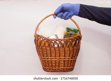 Home delivery. A blue-gloved delivery employee gives a basket of food and hygiene products. Protection against coronavirus COVID-19.