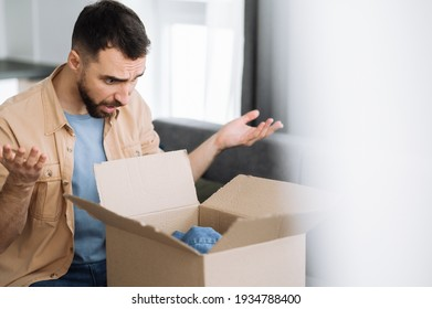 Home delivery. Confused young man sits on the couch, unpacking his parcel. Surprised caucasian male got a wrong order, unhappy guy bought stuff online, unsuccessful shopping concept